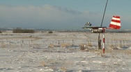 Stock Video Footage of weather vane on rural snow covered airstrip, #1