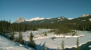 Stock Video Footage of river and waterfall, river and snow covered mountains, pan, Banff