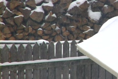 Snow Falling on Wood Pile and Rooftop Stock Footage