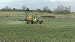Crop sprayer crosses a field of winter wheat, L to R Stock Footage
