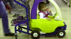 Little girl in moving shopping cart car Stock Footage