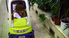 Little girl leaves shopping cart car near plants Stock Footage