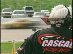 Motorsports, stock car, official in frame, race cars in background through frame Stock Footage