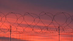 Barbed wire fence, red sky Stock Footage