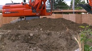 Construction, backhoe scooping dirt, #3 fence in bg Stock Footage