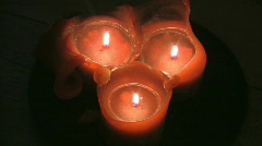 Three red candles burning in a dark room Stock Footage