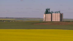 Agriculture, canola and wheat fields and grain elevator, #1 long Stock Footage