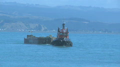 Tug pulling barge through harbor entrance Stock Footage