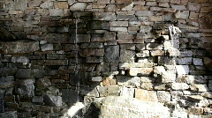 Water Falling Out of Rock Wall With Hard Angled Light Stock Footage