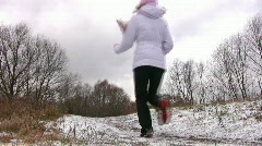 Woman running from camera on first snow way. Stock Footage