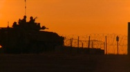 Stock Video Footage of military, silhouetted armored fight vehicle at sunset
