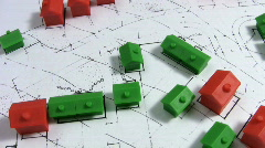 Rotating red and green model houses on a real estate housing plan. Stock Footage