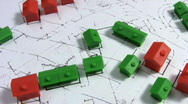 Stock Video Footage of Rotating red and green model houses on a real estate housing plan.