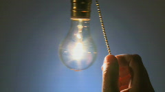 Hanging light bulb cu switched on 4b Stock Footage