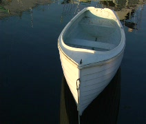 Rowboat drifting on calm water in marina tied Stock Footage