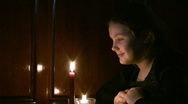 Stock Video Footage of girl the teenager looks at a burning candle.