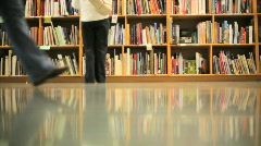 Shoppers in Front of Book Shelves in Book Store Stock Footage