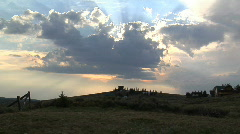 Heavenly Clouds Pass Before a Setting Sun Above a Rural Landscape Timelapse Stock Footage