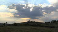 Stock Video Footage of Heavenly Clouds Pass Before a Setting Sun Above a Rural Landscape Timelapse