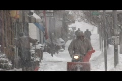 Snow blowing on downtown sidewalk during snowstorm Stock Footage
