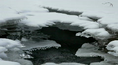 Water streams while ice grows on the banks of a small  river Stock Footage
