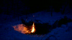 A man goes to a fire burning in the snow on a winter night Stock Footage