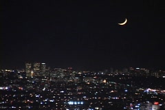 A new moon dominates the night sky over the city of Los Angeles. Stock Footage