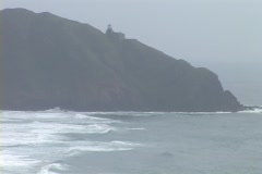 A distant lighthouse shines in the fog atop a rocky coastline. Stock Footage