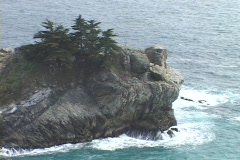 Waves break on a small rocky island off the Big Sur coast of California. Stock Footage