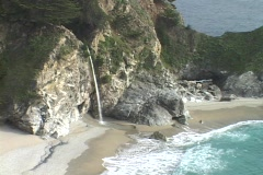 Gentle waves and a waterfall wash the sand on the shore of a rocky Big Sur Stock Footage