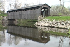 A covered bridge reflects in a Madison County river. Stock Footage