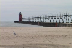 A lighthouse stands at the end of a pier in Grand Haven, Michigan. Stock Footage