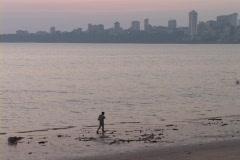 A person walks along the beach near Mumbai, India. - stock footage