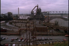 A sprawling raw materials plant pumps out steam. Stock Footage