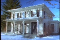 Snow covers the ground in front of an old house. Stock Footage