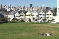 A man lounges on the grass in a Victorian neighborhood in San Francisco, Stock Footage
