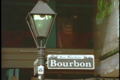 A Bourbon street sign hangs on a lamppost. - stock footage