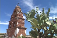 A cactus stands beside a bell tower at an old Catholic mission. - stock footage