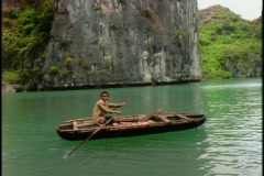 A Vietnamese boy rows a boat on green water in Halong Bay, Vietnam. Stock Footage