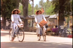 Girls ride on bicycles in traditional Vietnamese dresses Stock Footage