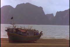 A Vietnamese fishing boat sits in dry-dock on a beach at low tide. Stock Footage