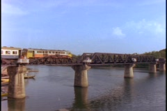 An old-fashioned Asian passenger train crosses the bridge at the river Kwai. Stock Footage