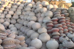 A man stacks pots in an enormous pile of pottery. Stock Footage