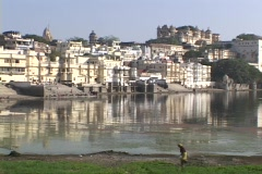 A pedestrian walks by a lake near the palaces in Udaipur, India. Stock Footage