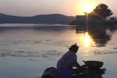 A woman washes clothes at golden-hour next to a lake. Stock Footage