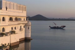 A boat floats on a lake near a palace in Udaipur, India. Stock Footage