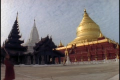 A pedestrian walks in front of a Buddhist temple in Burma. Stock Footage