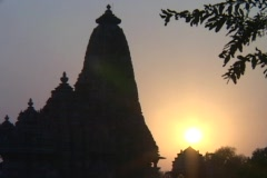 A spire on an Indian temple stands silhouetted against the sun. Stock Footage