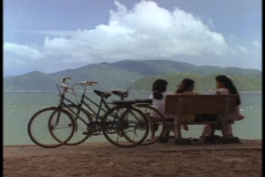 Vietnamese schoolgirls sit on bench overlooking the South China Sea. Stock Footage