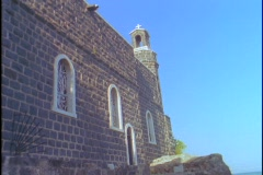 A Catholic priest stands and looks into the distance near the Sea of Galilee. Stock Footage